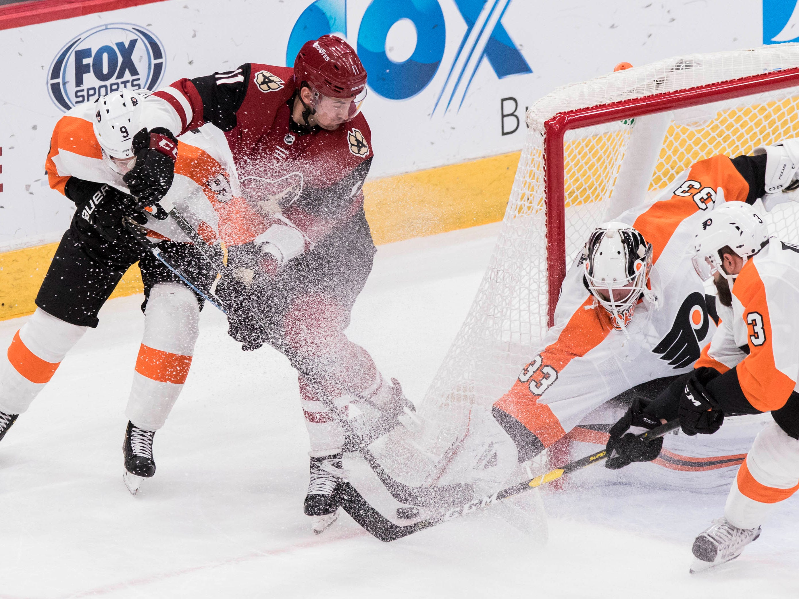 Arizona Coyotes' Brendan Perlini (11) and the Philadelphia Flyers' Ivan Provorov (9) and goalie Calvin Pickard (33) fight for the puck during the second period of an NHL hockey game Monday, Nov. 5, 2018, in Glendale, Ariz. (AP Photo/Darryl Webb)