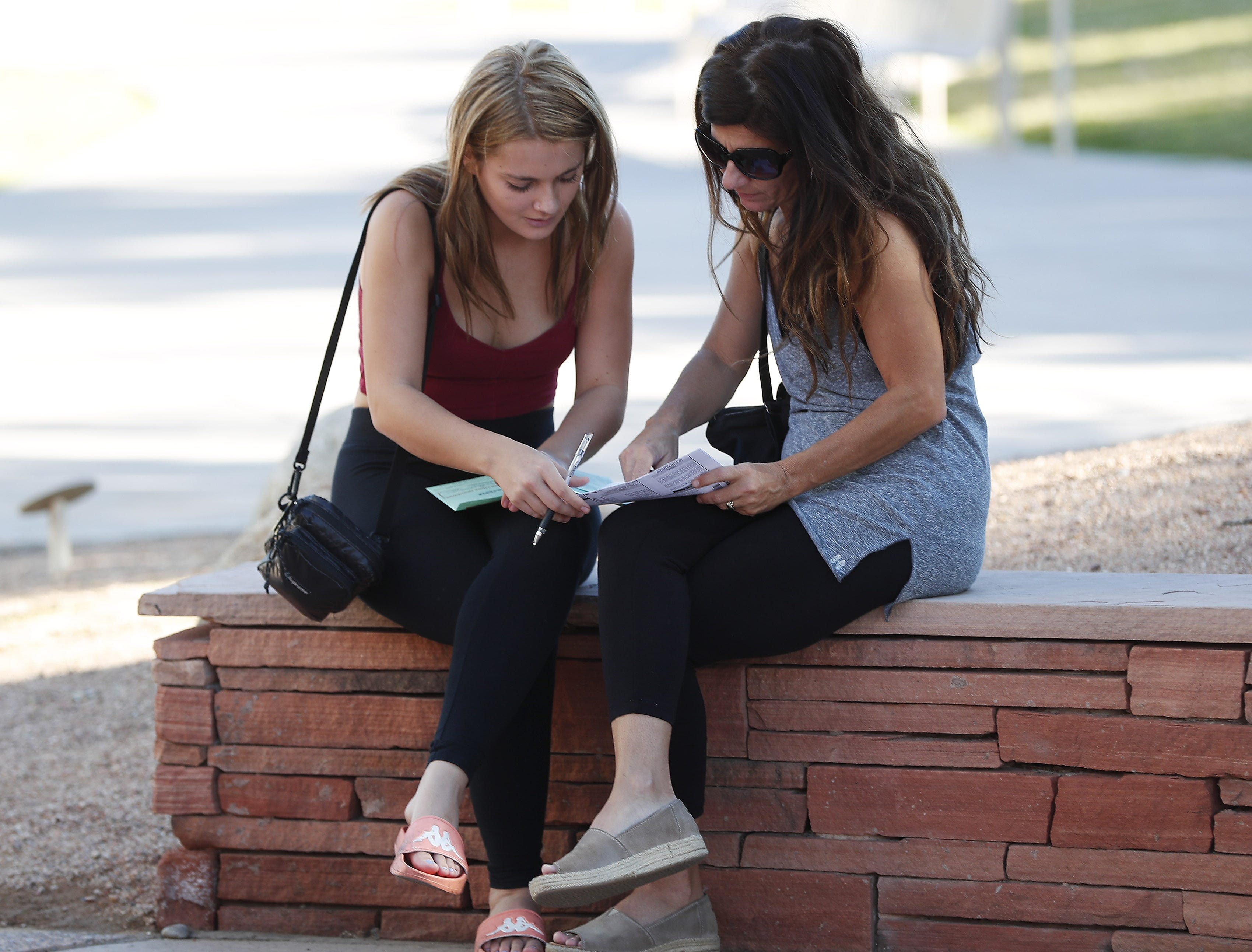 Eve Beresford, 18, gets help filling out her early ballot from her mom, Celia, outside a polling station at the Tempe History Museum in Arizona on Nov. 6, 2018.
