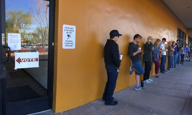 Voters wait in line near the Gila polling site in Chandler. The poll workers were locked out of the site after the tenant did not pay their rent. Workers moved the polling site to the south side of the building in an empty suite, Nov. 6, 2018.