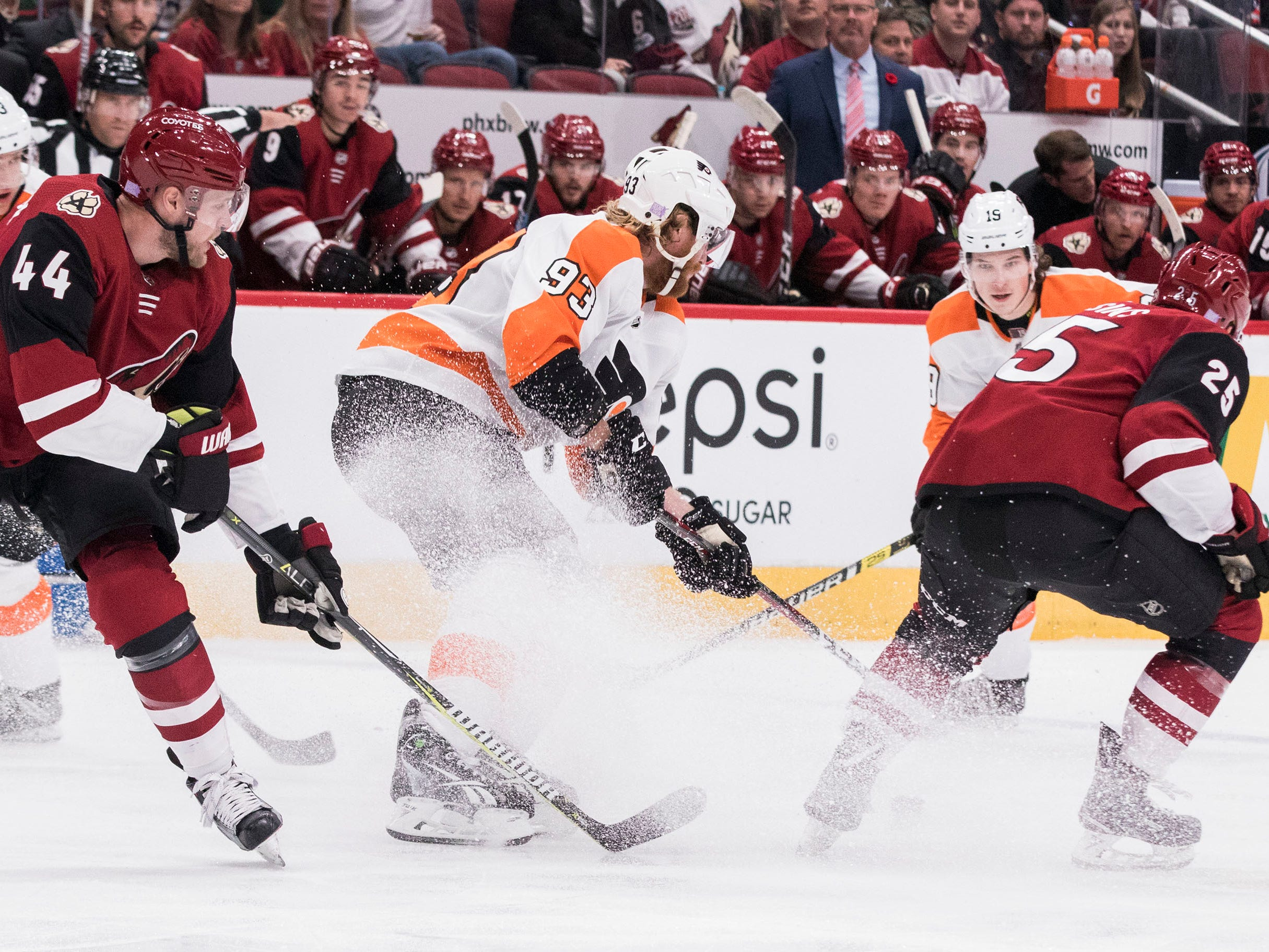 Philadelphia Flyers' Jakub Voracek (93) controls the puck as he's double-teamed by the Arizona Coyotes' Kevin Connauton (44) and Nick Cousins (25)during the first period of an NHL hockey game Monday, Nov. 5, 2018, in Glendale, Ariz. (AP Photo/Darryl Webb)