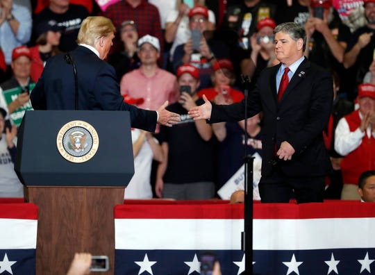 President Donald Trump shakes hands with Fox News host Sean Hannity (right) during a campaign rally Nov. 5, 2018, in Cape Girardeau, Missouri.