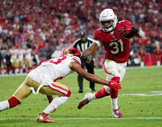 Arizona Cardinals running back David Johnson (31) pushes away San Francisco 49ers cornerback Ahkello Witherspoon (23) during a run in the fourth quarter on Oct. 28 at State Farm Stadium.