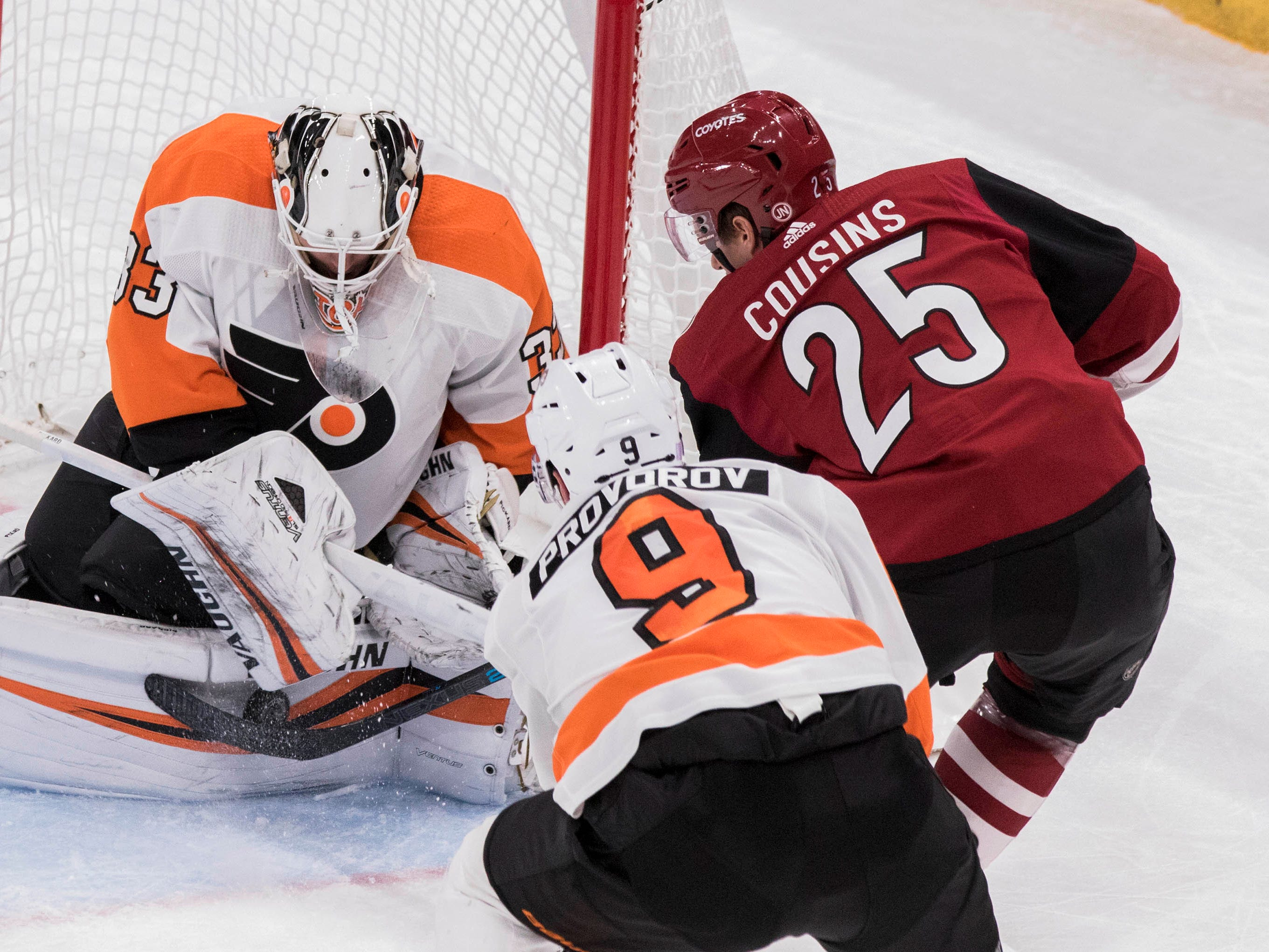 Arizona Coyotes' Nick Cousins (25) puts the puck against the pads of Philadelphia Flyers goalie Calvin Pickard (33) as teammate Ivan Provorov (9) looks on during the third period of an NHL hockey game Monday, Nov. 5, 2018, in Glendale, Ariz. (AP Photo/Darryl Webb)