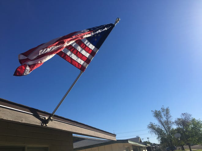 Before I left the house on Tuesday, I put up the flag, sliding it into the bracket over the front door, and stood back to watch it, flapping in the morning breeze.
