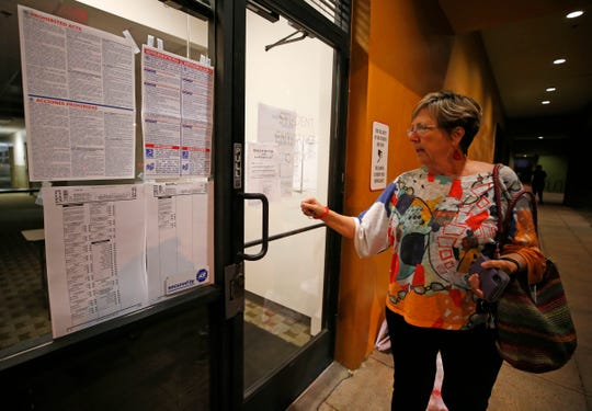 Inspector Eileen Wendt looks at a sign from the landlord that says the tenant did not pay rent and the locks have been changed preventing access to the Gila polling place in Chandler, Nov. 6, 2018.