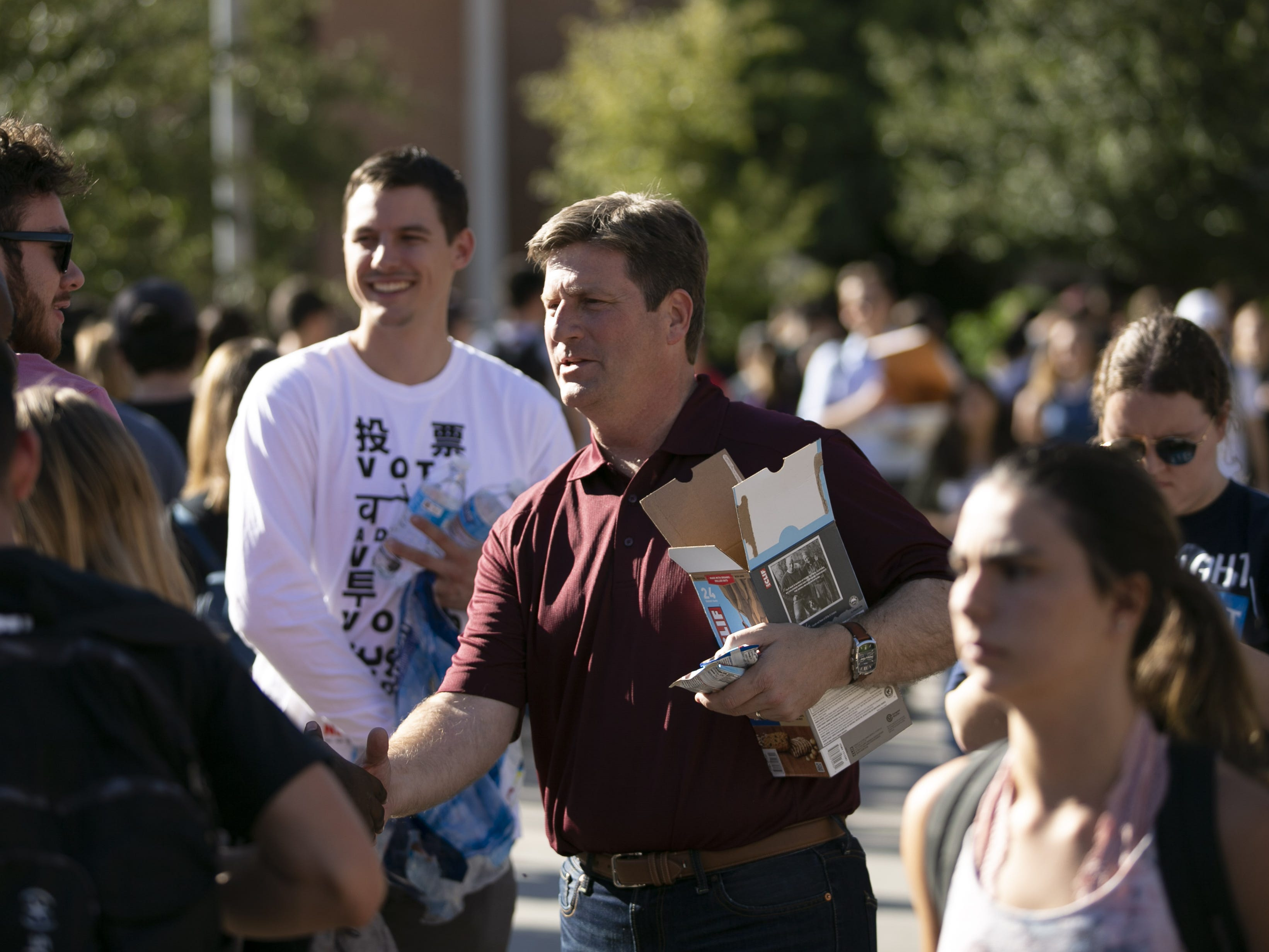 Greg Stanton, a Democrat running for U.S. Congress in Arizona's 9th Congressional District, shakes hands with Arizona State University students as they wait in line to vote at the polling place at ASU's Tempe campus on Nov. 6, 2018.