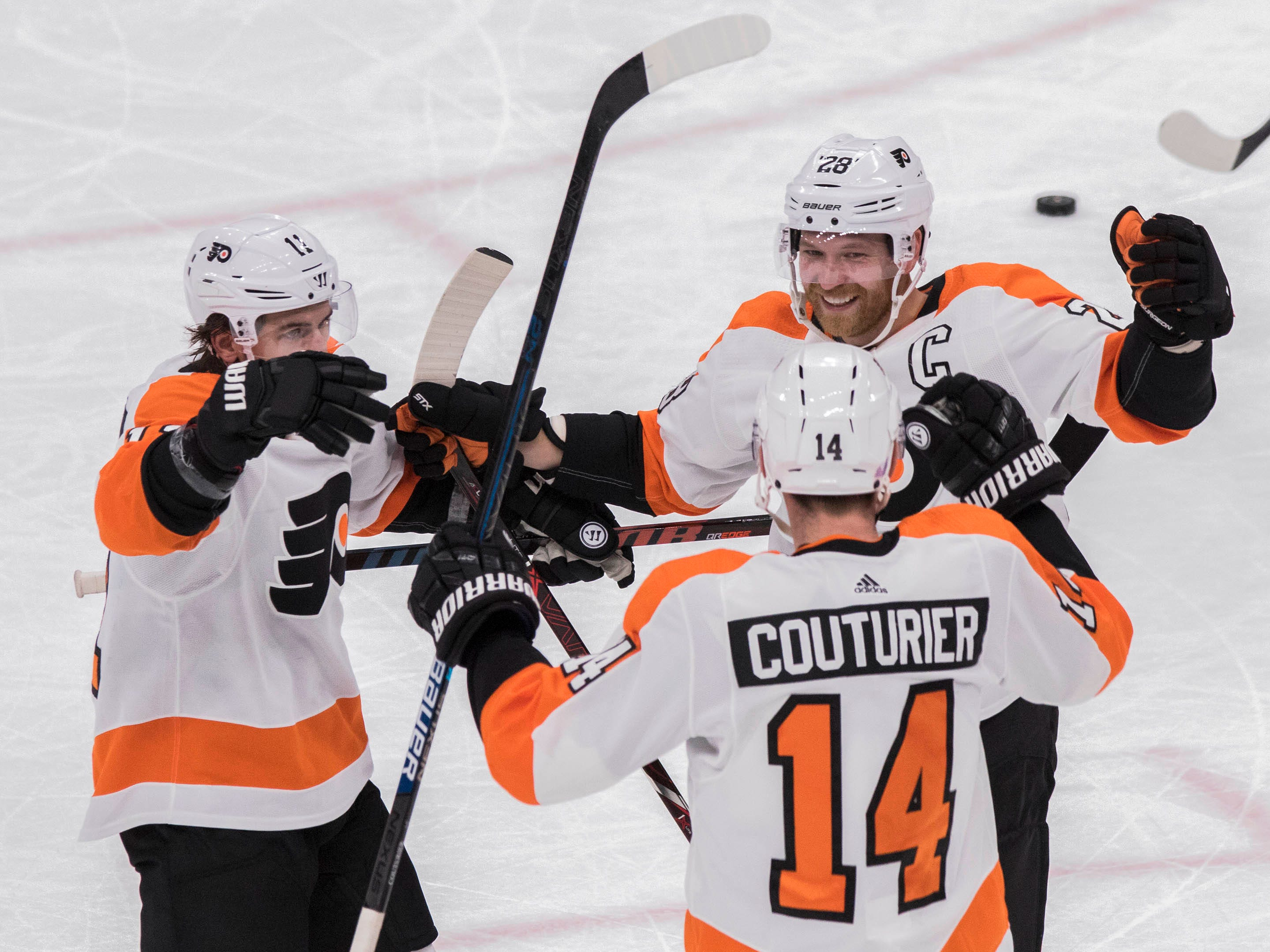 Philadelphia Flyers' Travis Konecny (11) Claude Giroux (28) congratulate Sean Couturier (14) after he scored against the Arizona Coyotes during the second period of an NHL hockey game Monday, Nov. 5, 2018, in Glendale, Ariz. (AP Photo/Darryl Webb)