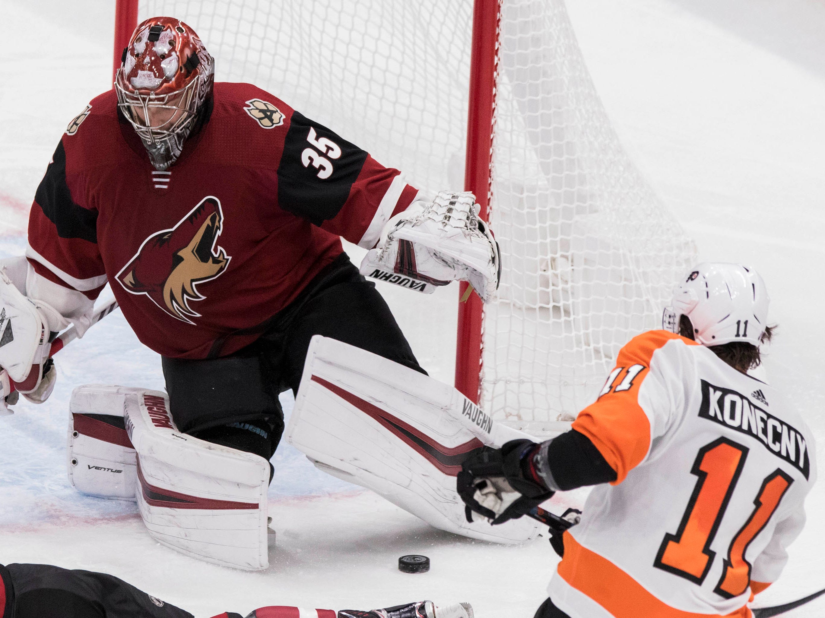 Arizona Coyotes goalie Darcy Kuemper (35) deflects a shot from the Philadelphia Flyers' Travis Konecny (11) during the second period of an NHL hockey game Monday, Nov. 5, 2018, in Glendale, Ariz. (AP Photo/Darryl Webb)