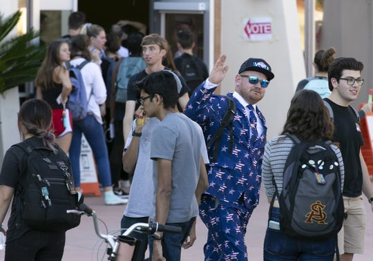 Arizona State University student Urban Stewart (center right) high fives other ASU students as they wait in line to vote at the polling place at ASU's Tempe campus on Nov. 6, 2018.