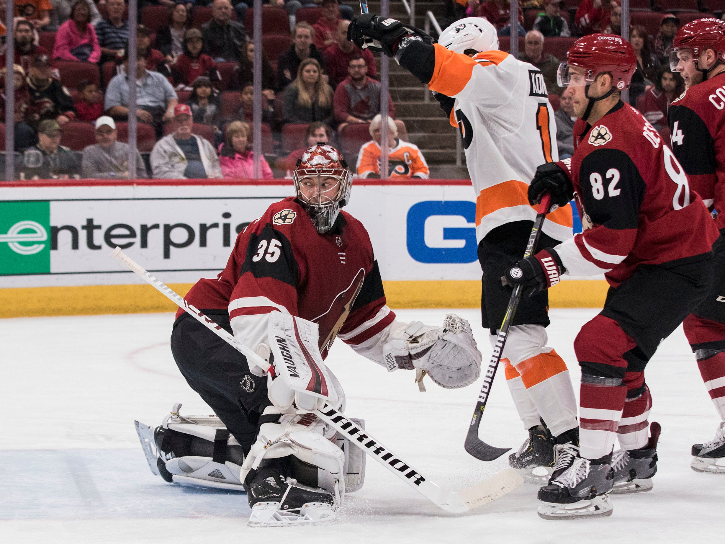 Philadelphia Flyers' Travis Konecny, center, celebrates his goal as the Arizona Coyotes goalie Darcy Kuemper, left, and Jordan Oesterle, right, looks back towards the net during the first period of an NHL hockey game Monday, Nov. 5, 2018, in Glendale, Ariz. (AP Photo/Darryl Webb)