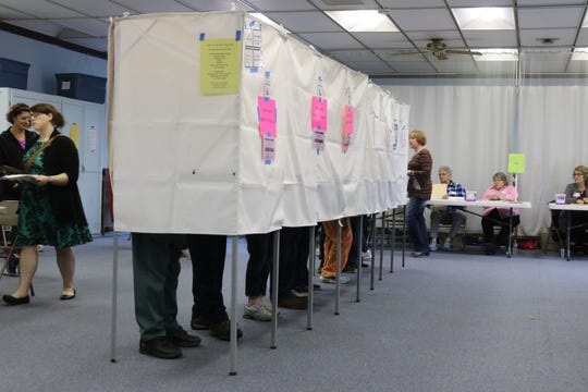 Voters in Port Clinton fill out there ballots at the busy polling location in Peace Lutheran Church on Tuesday.