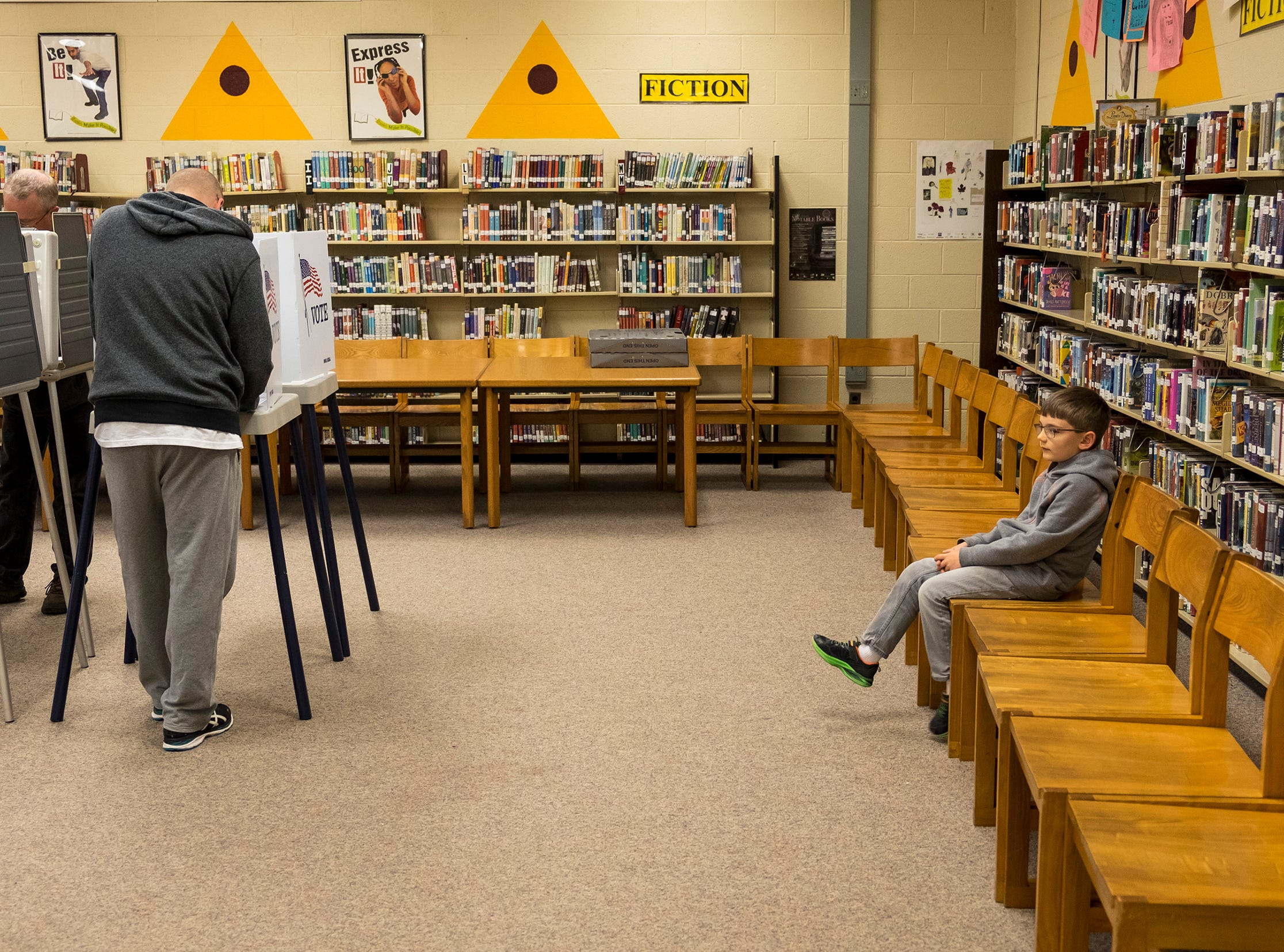 Zona Priess, 6, waits while his father Mark, left, fills out his ballot Tuesday, Nov. 6, 2018 at the precinct 2 voting location at Fort Gratiot Middle School.