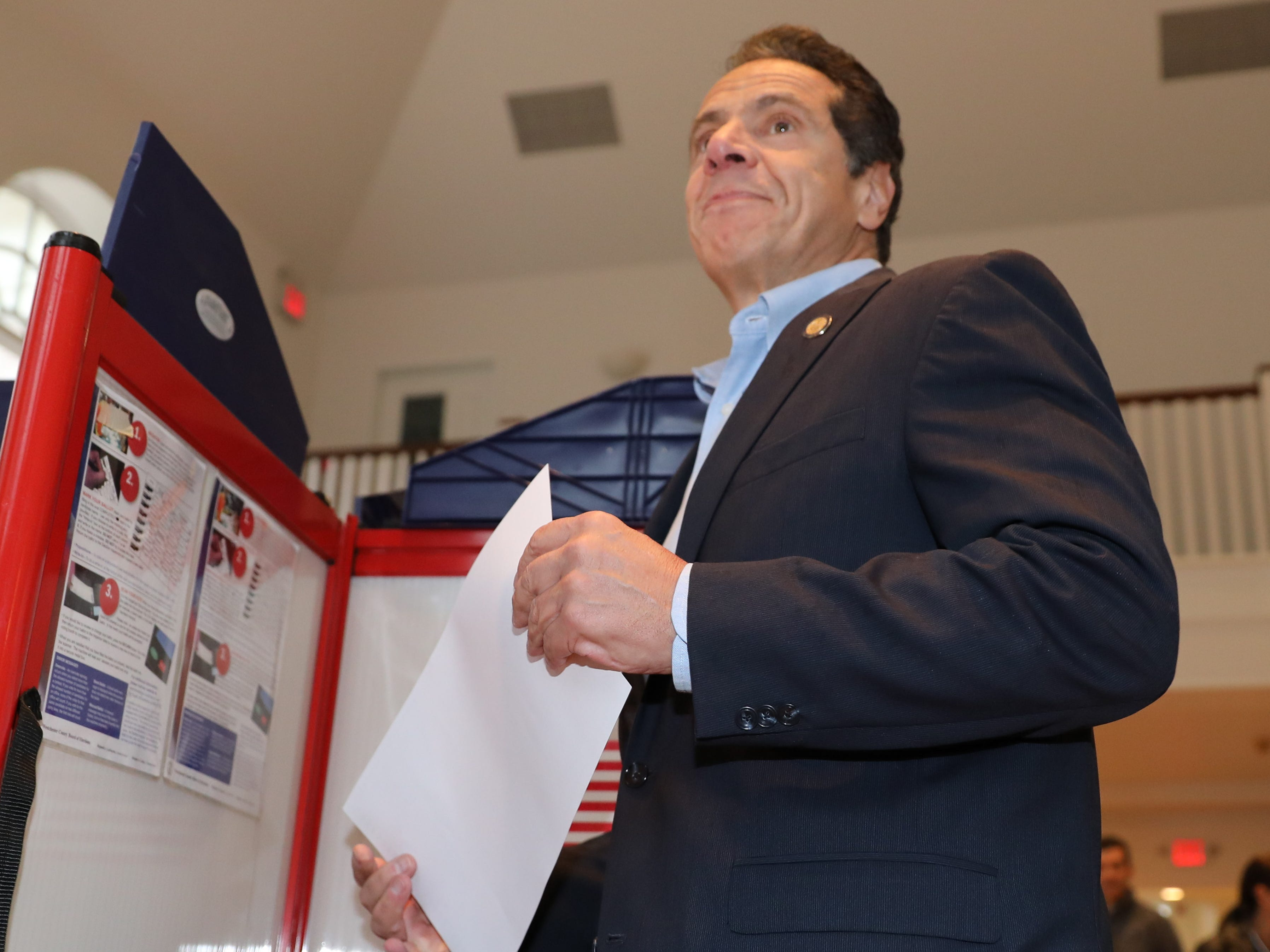 New York Gov. Andrew Cuomo heads toward a privacy table as he prepares to vote Tuesday at the Presbyterian Church of Mount Kisco.