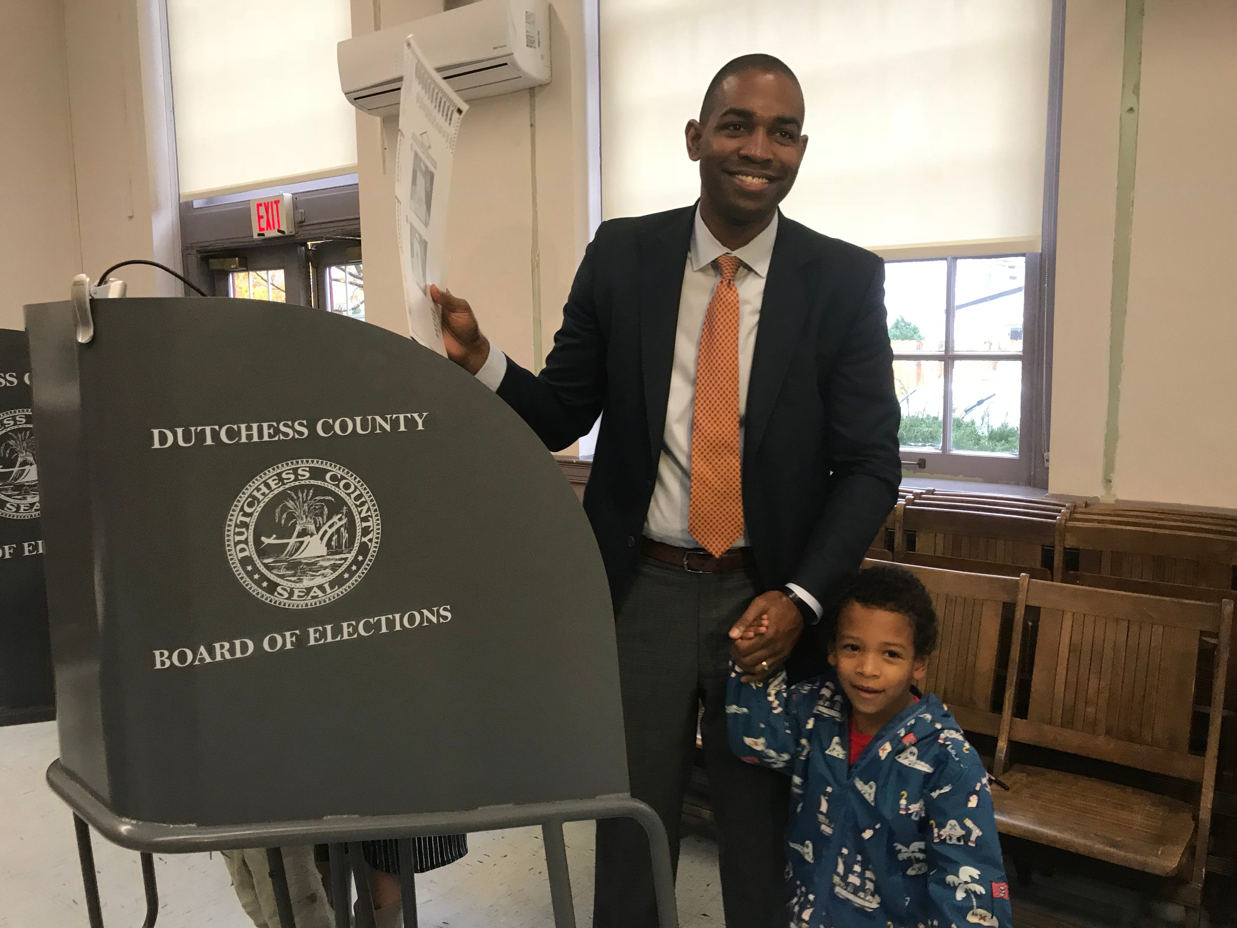 With his 5-year-old son Coltrane by his side, Antonio Delgado of Rhinebeck, candidate for the 19th Congressional District, votes at Rhinebeck Town Hall Tuesday morning.