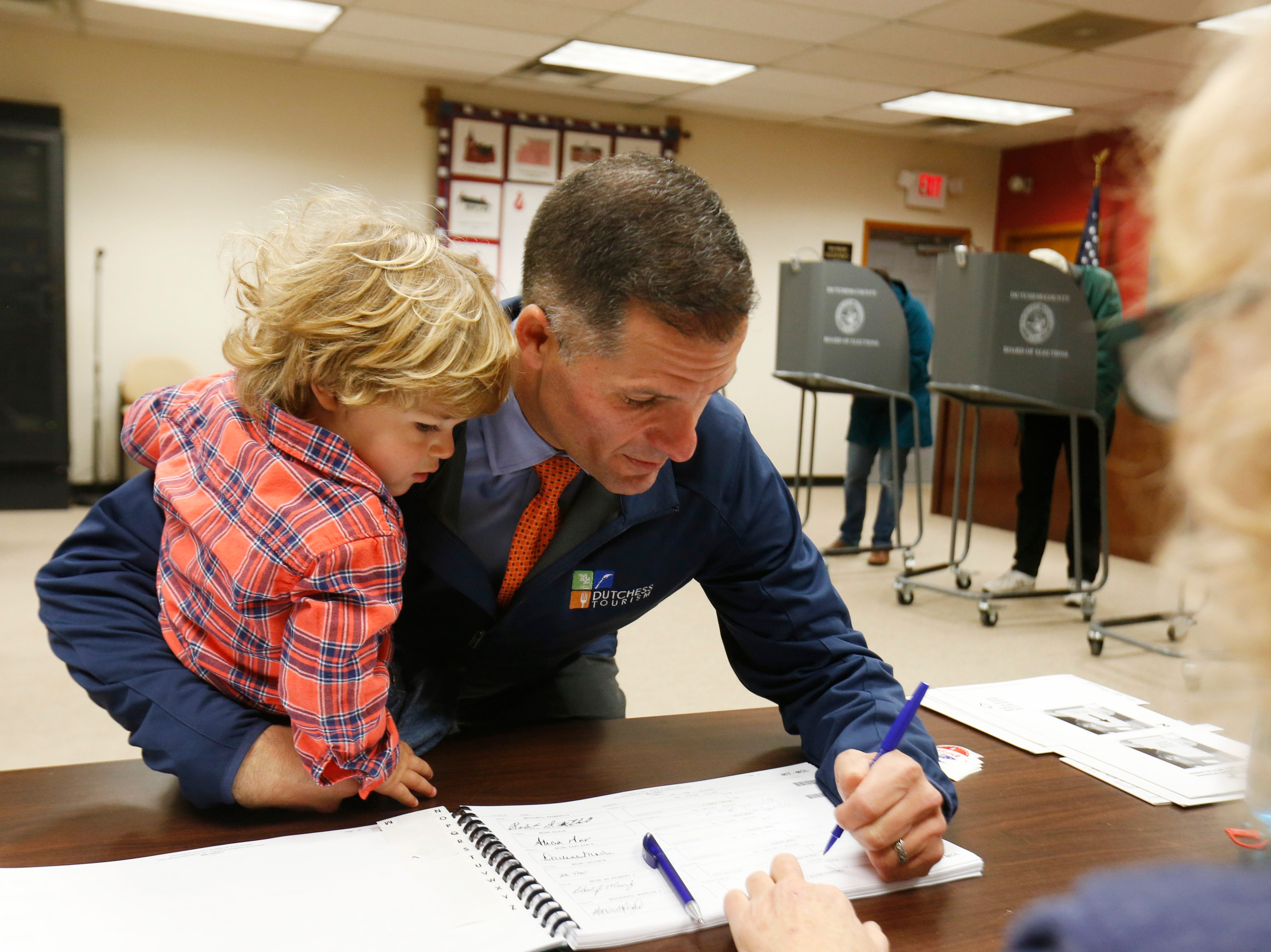 Republican Gubernatorial candidate Marc Molinaro holding his son, Elias, checks in at  Red Hook Town Hall to cast his ballot on November 6, 2018.