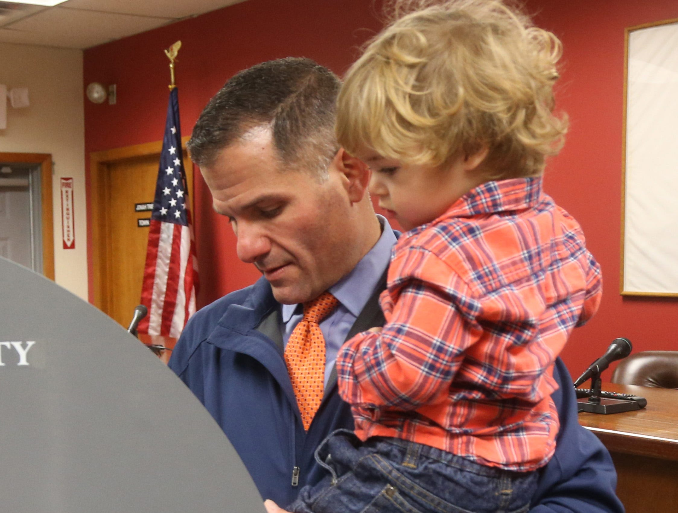 Republican Gubernatorial candidate Marc Molinaro holding his son, Elias, fills in his ballot at Red Hook Town Hall on November 6, 2018.