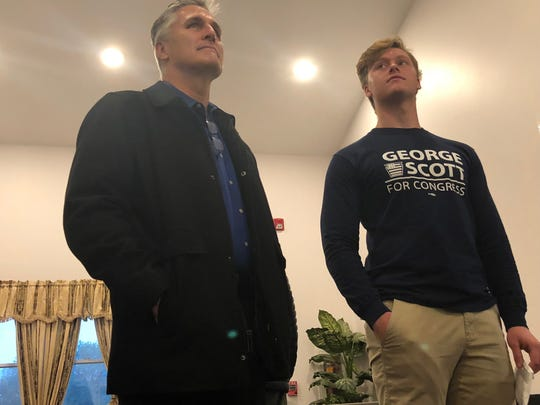 George Scott stands with son, Nicholas Scott, waiting to cast their ballots Election Day.