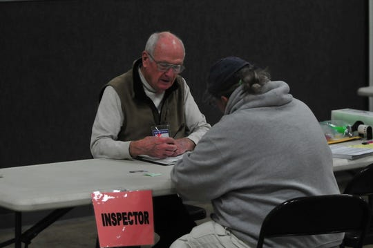 Inspector Bill Martus helps a voter Tuesday at Kuhlman Center. Martus has been a poll worker for 20 years.