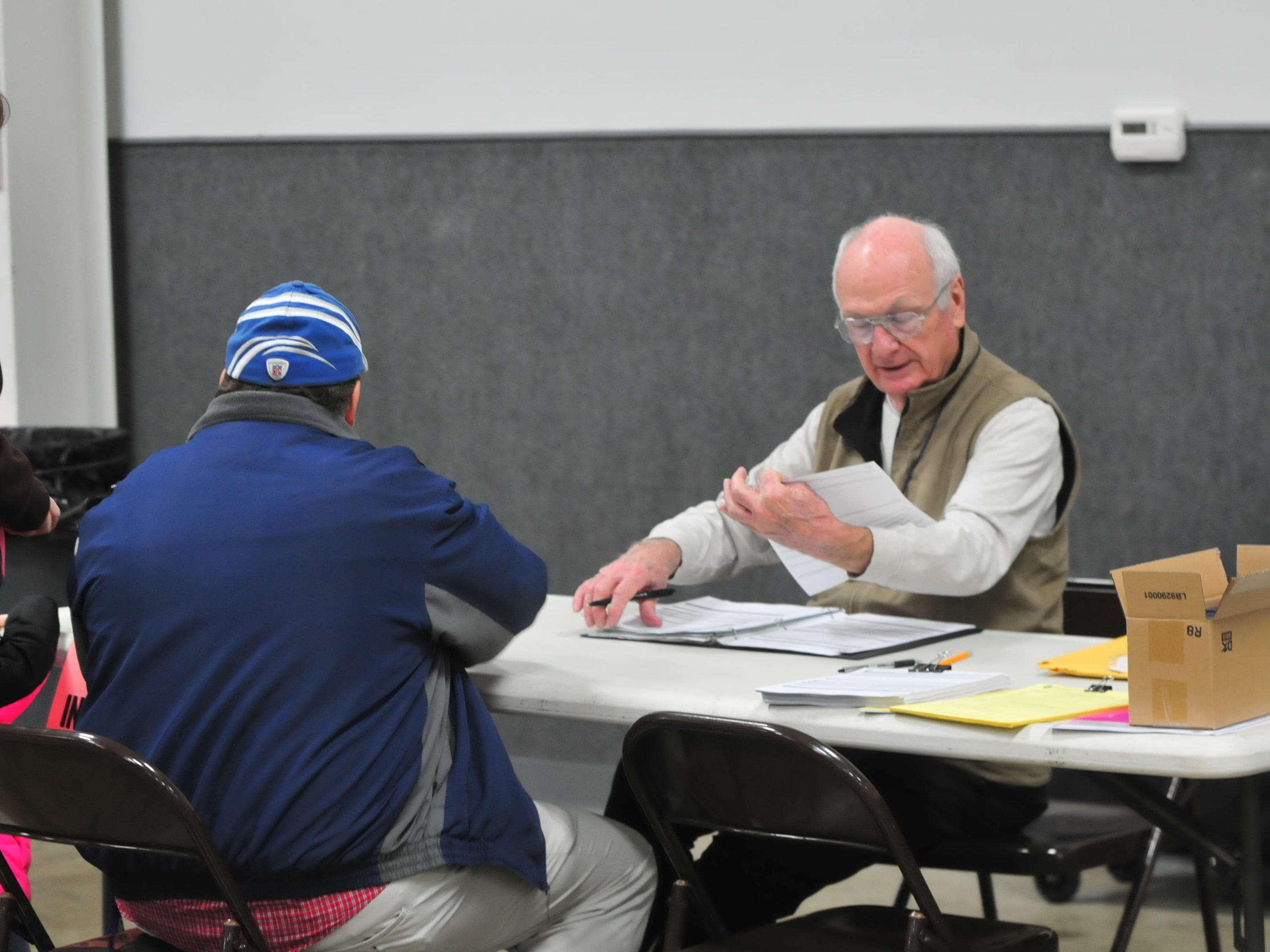 Bill Martus checks some paperwork in his role as inspector for the vote center inside Kuhlman Center.