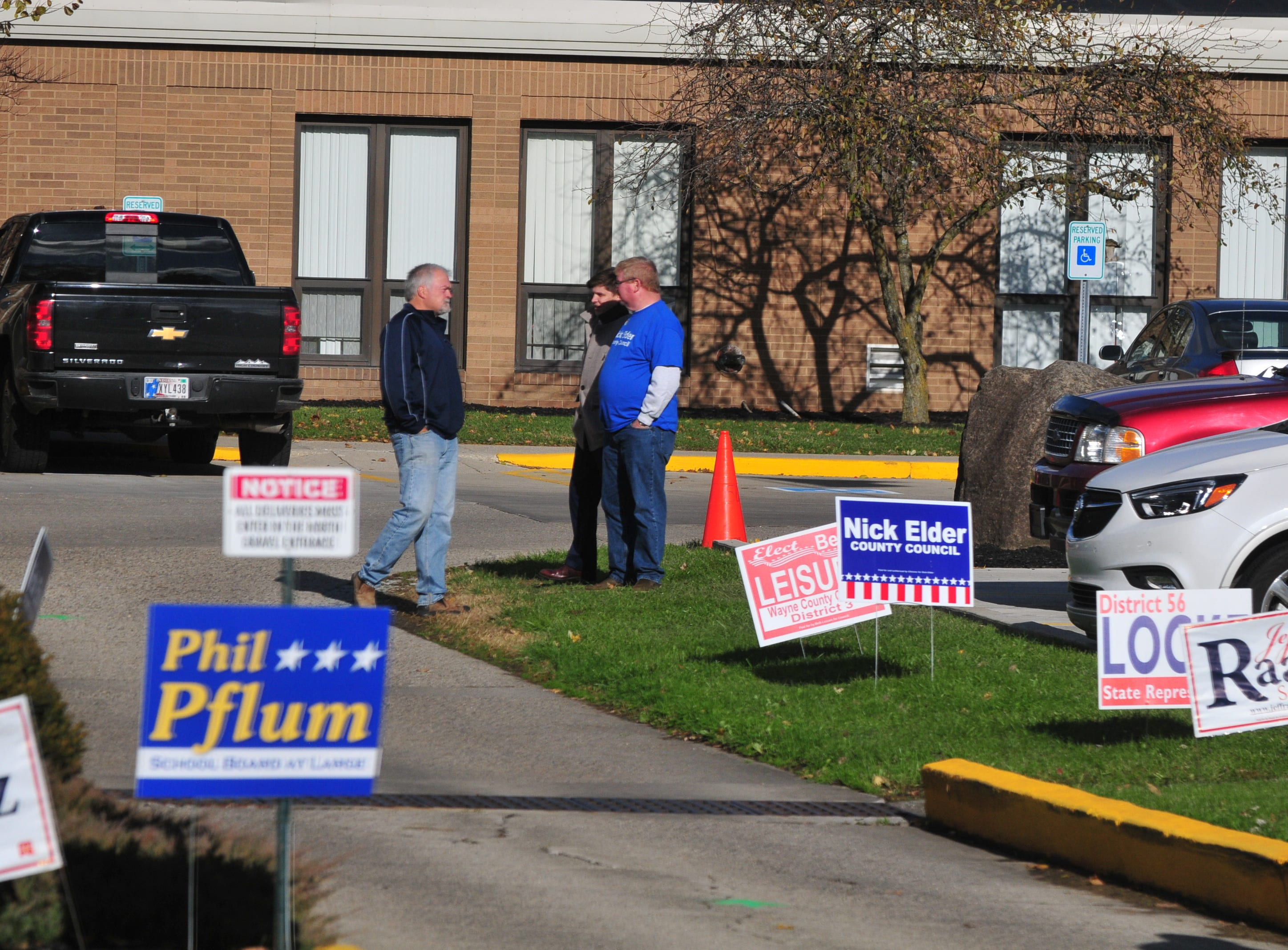 Republican candidate for state representative Brad Barrett (left) and Democratic candidate for Wayne County Council Nick Elder (center) chat outside the vote center at the Golay Center in Cambridge City on Tuesday, Nov. 6, 2018.