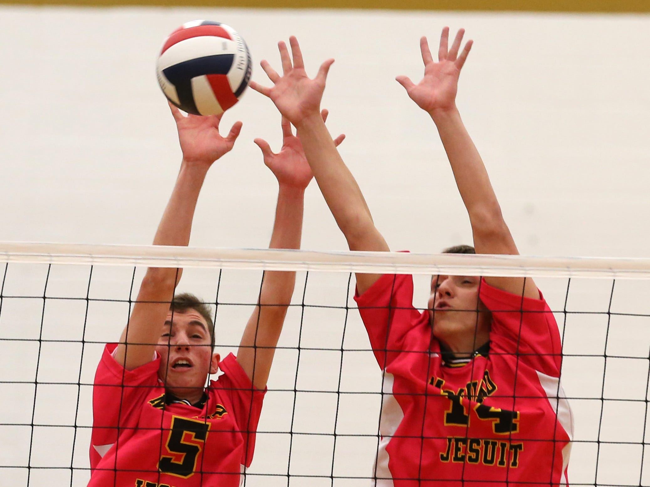 McQuaid's Christopher Mahar, left, and Christian Pawelek form a wall and block a spike by Penfield's Jack Bittker during the 2015 Section V Class A championship match at Victor.