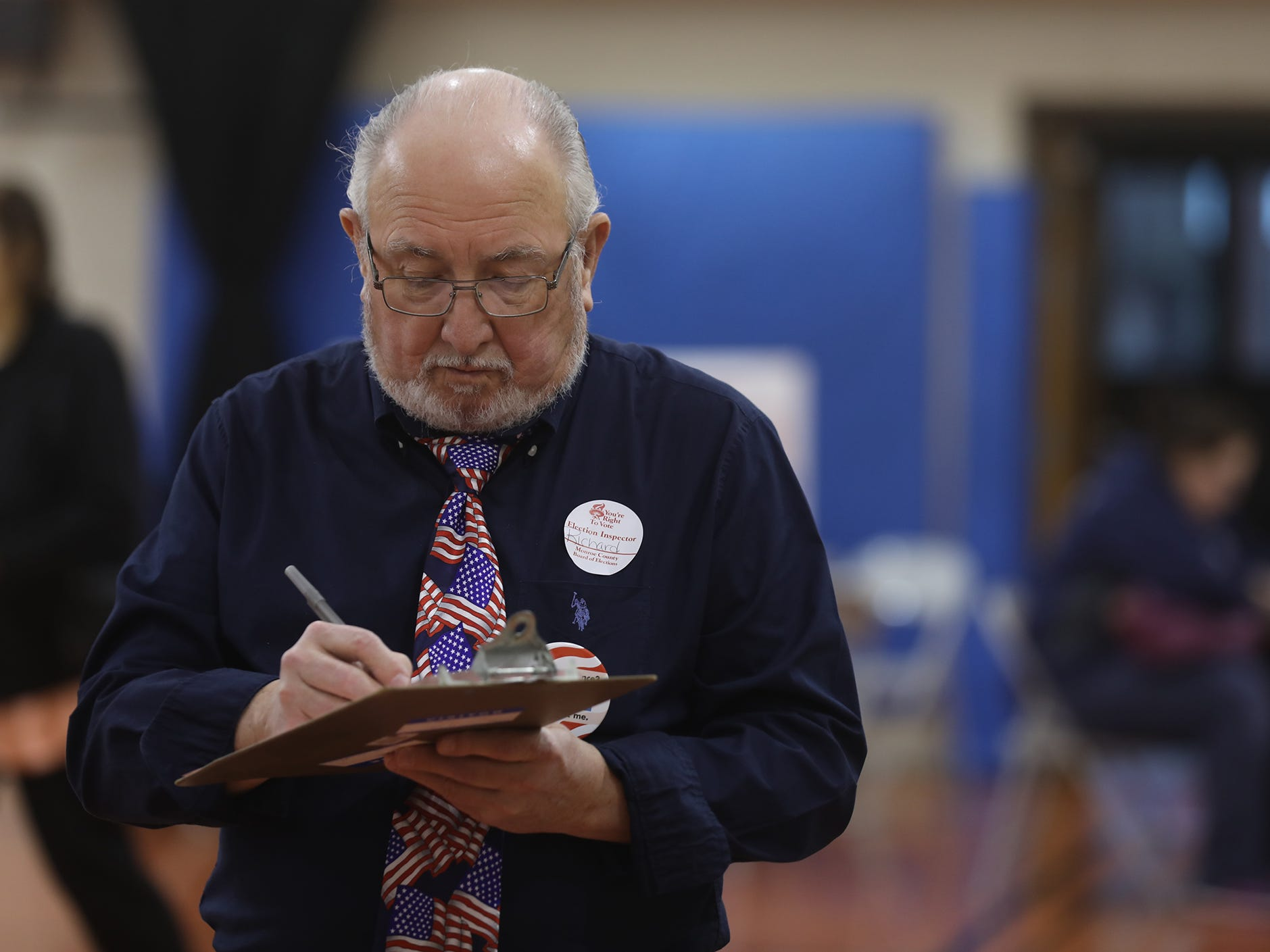 Richard Astifan signs a certificate of service that says he took the oath as part of being an election inspector and is working on Election Day, Nov. 6, 2018.  Astifan was one of several workers at the United Methodist Church in Webster.