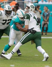 "Miami Dolphins defensive end Cameron Wake (91) sacks New York Jets quarterback Sam Darnold (14). Darnold was sacked four times and threw four interceptions in the 13-6 loss. ""Stupid football'' he said when describing his performance. He faces the Bills and possibly fellow Class of 2018 quarterback Josh Allen on Sunday."