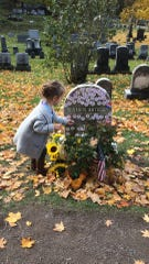 Nora Ray puts her mother's sticker on Susan B. Anthony's grave in Mt. Hope Cemetery on Election Day, Nov. 6, 2018.