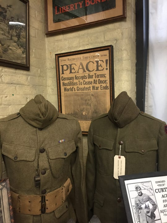 The Military History Society displays the front page of the Democrat and Chronicle for Nov. 12, 1918 in the background.