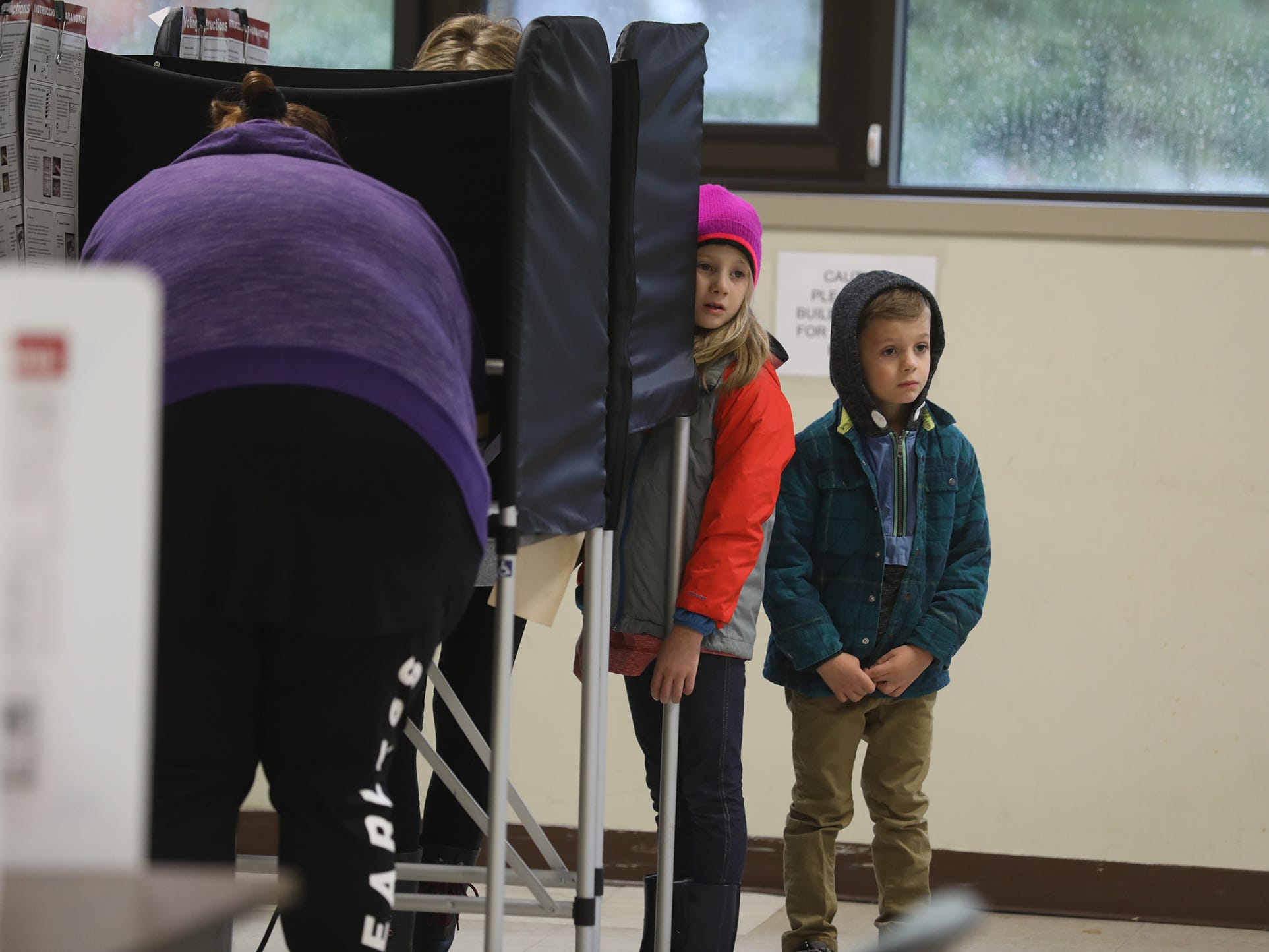 Lucy Teeter and her brother, Finn, look around the room while waiting for their mother, Ashley, to finish voting at Penfield Community Center.