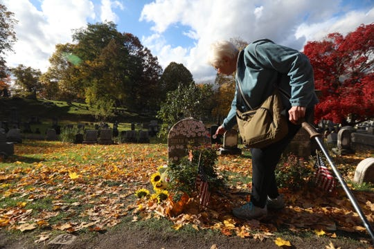 Joanne Mitchell, a volunteer at Mt. Hope Cemetery for the past 10 years, puts her sticker on Susan B. Anthony's grave on Election Day, Nov. 6, 2018.