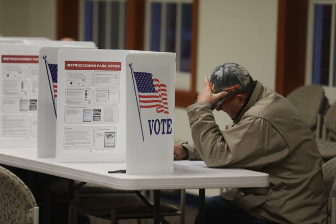 Bill Fehr carefully goes over his ballot in PIttsford.