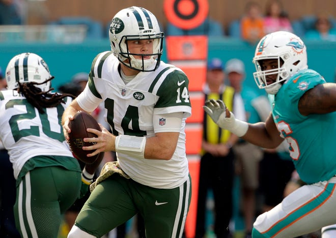 Jets quarterback Sam Darnold (14) looks to pass, during the first half of an NFL football game against the Miami Dolphins in Miami Gardens, Fla. Many teams think it's best to throw rookie QBs right into the fire to learn on the job. Others prefer to gradually work them into the offense. Then, there are some who believe it's more beneficial to have them grab a cap and a clipboard and take it all in from the sideline.