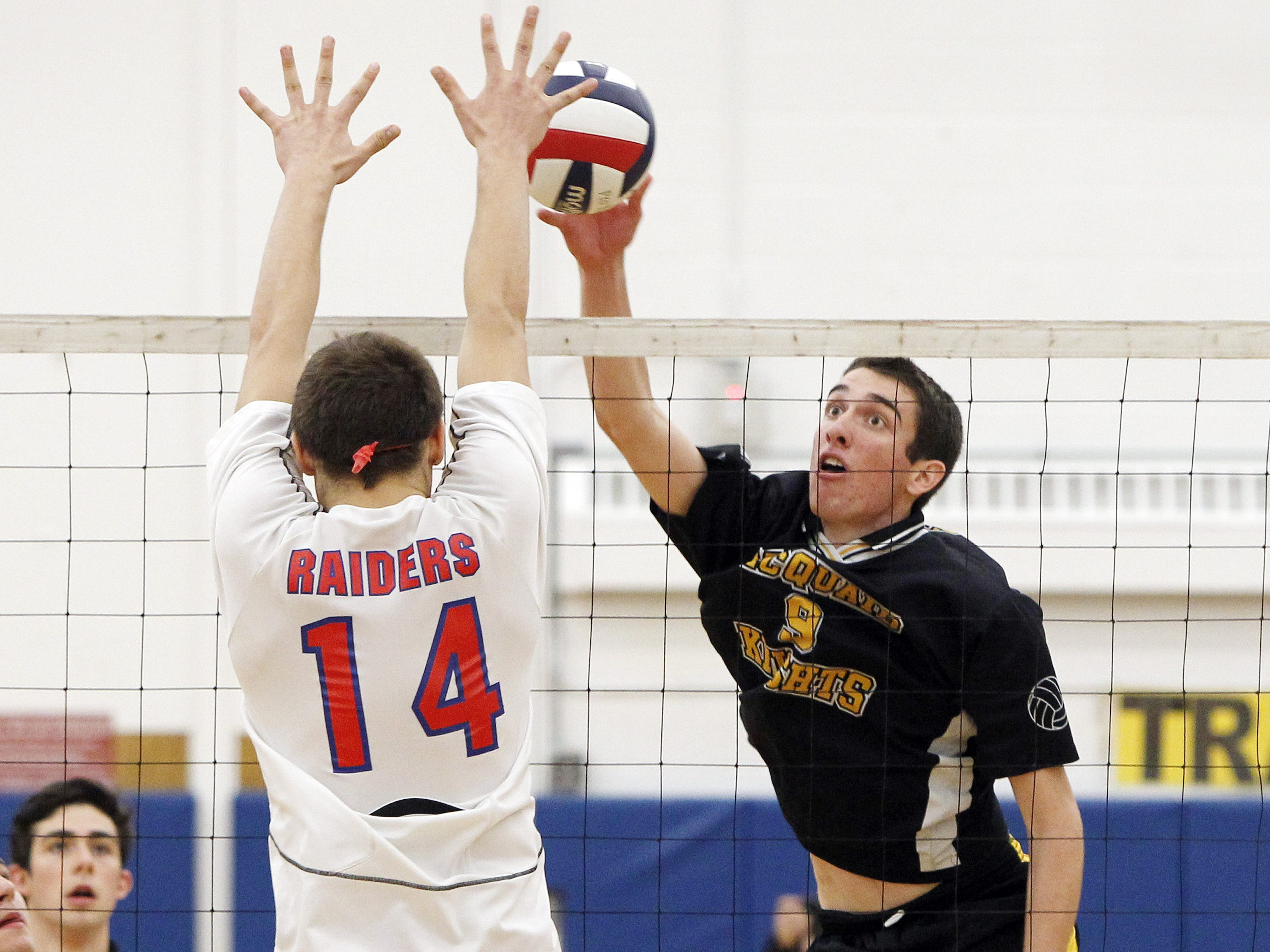 McQuaid's Colin Murphy, right, looks to put a shot past Fairport's Josh Holm during Section V Class A boys volleyball championship action between the McQuaid Jesuit Knights and the Fairport Red Raiders at Webster Schroeder high school Thursday evening, November 7, 2013.