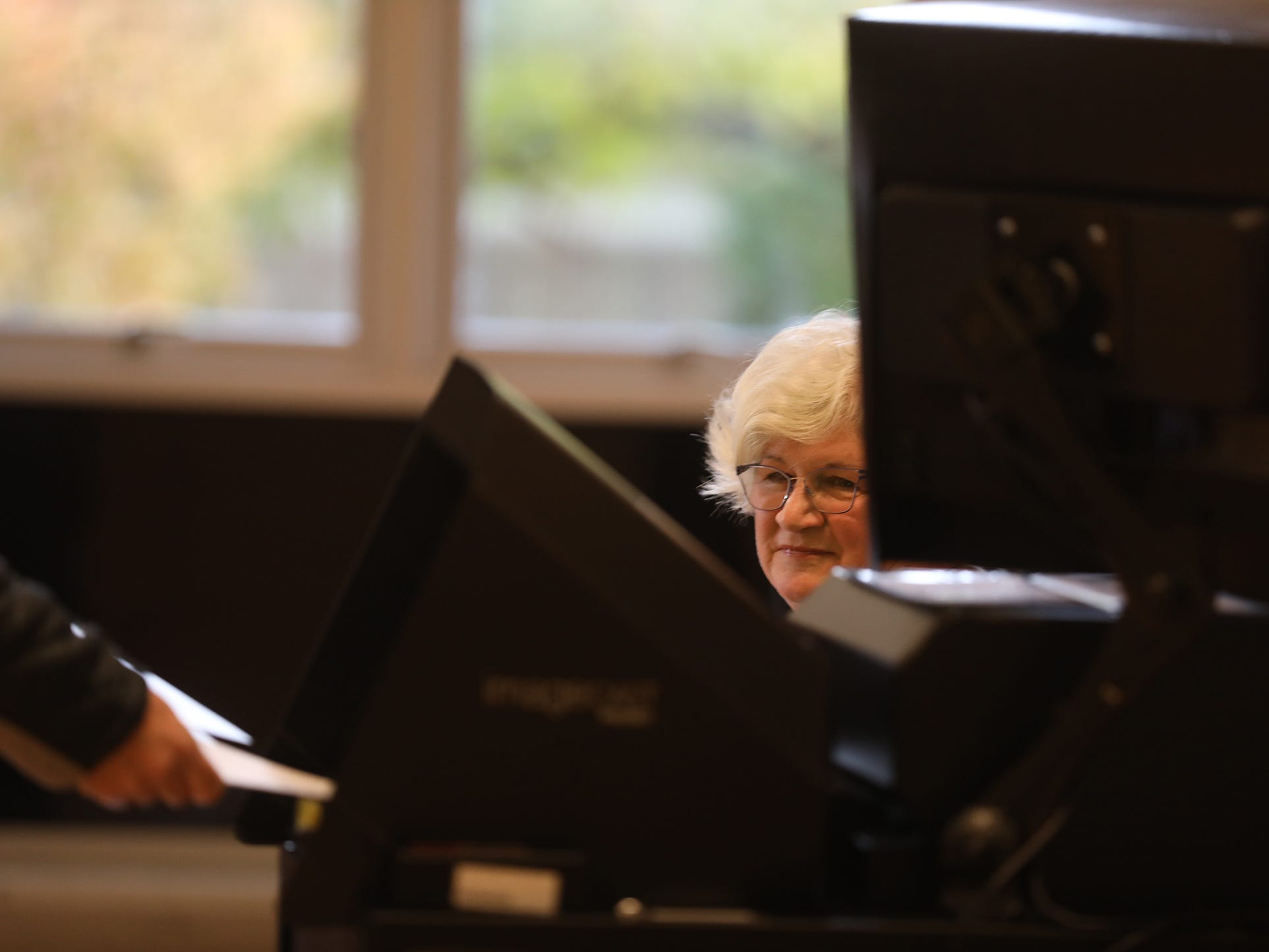 Karen Williams, an elecction inspector at Aldersgate united Methodist Church in Greece, watches as a ballot gets put into the voting machine.