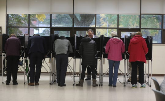 The standing booths for voters to fill out their ballots are filled with early morning voters at Penfield Community Center.