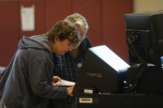 After Laurie Brown casts her ballot in the gym at Aldersgate United Methodist Church in Greece.  She and her husband, Mike, watch to make sure the machine accepts it.