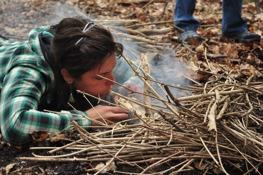Lindsay Cray demonstrates friction fire-making for a class.