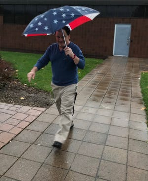 Voter Mark Thompson turning out early Tuesday at the Penfield Community Center, despite morning showers.
