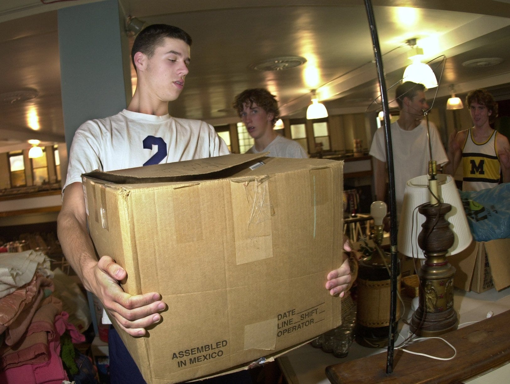 McQuaid volleyball star Dan O'Dell, together with teammates, helps organize a sale at Blessed Sacrament moving boxes and setting up tables. Friday Sept,. 7 2001.