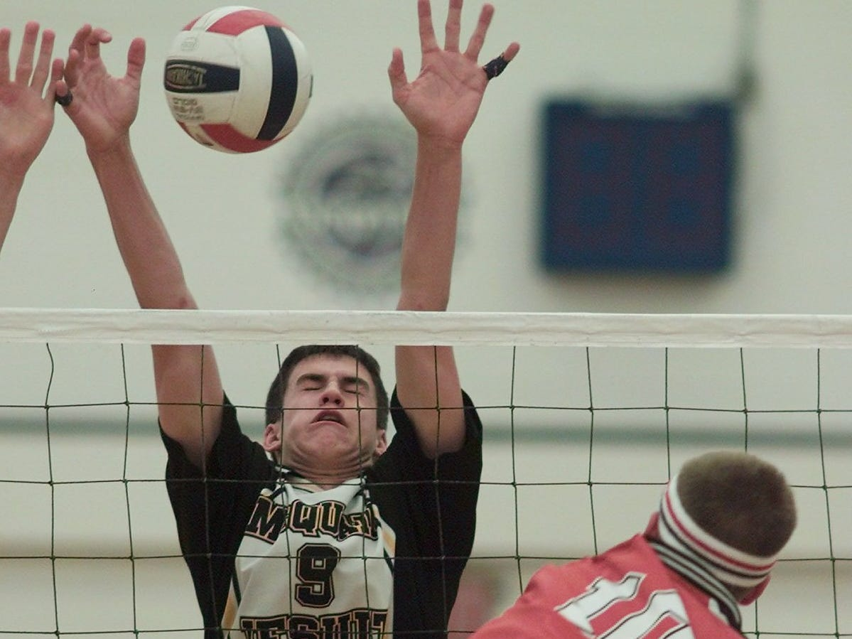McQuaid's AJ Nally goes up to block a shot by Penfield's Nathan Chambery (10) during the 2004 Class A volleyball finals.