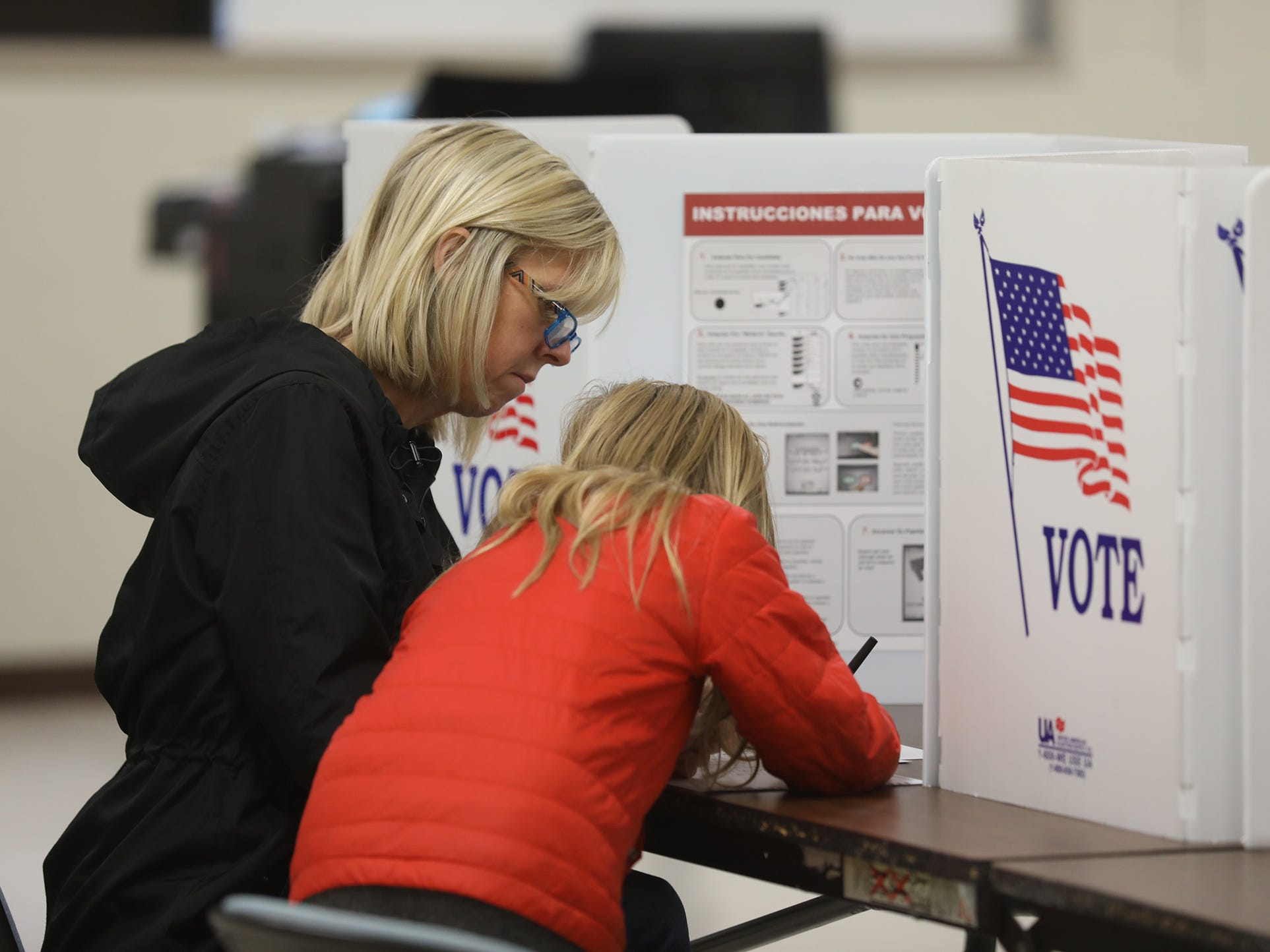 Aubrin Crowley, 9, helps her mother Michelle, vote at the Penfield Community Center.  She filled in the ballot at the spots her mother pointed at.