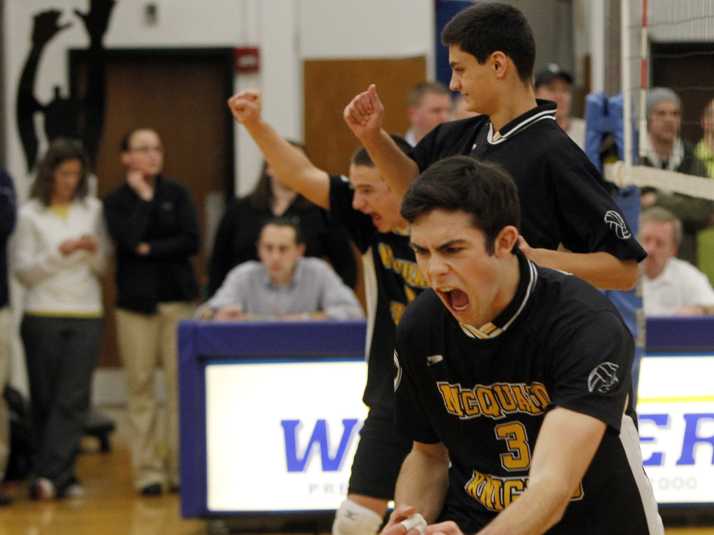 McQuaid's Colby Harriman, front, is fired up after a kill during Section V Class A boys volleyball championship action between the McQuaid Jesuit Knights and the Fairport Red Raiders at Webster Schroeder high school Thursday evening, Nov. 7, 2013.