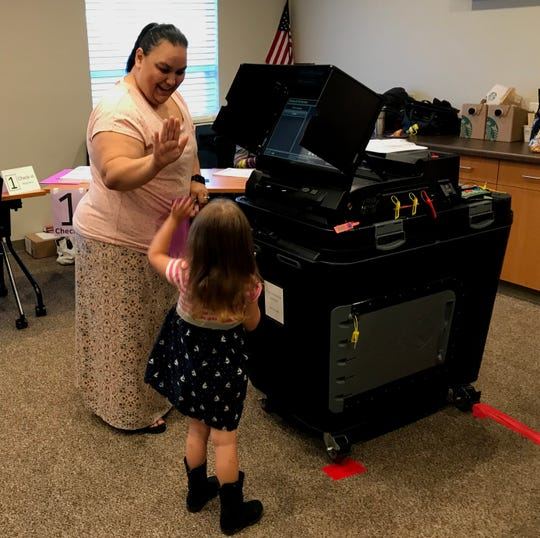 Milli Israel high-fives her daughter, Mariana, after casting her ballot.