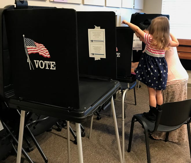 Four-year-old Mariana Israel of Shasta Lake helps her mom, Milli, cast her votes Tuesday at the John Beaudet Community Center in Shasta Lake.