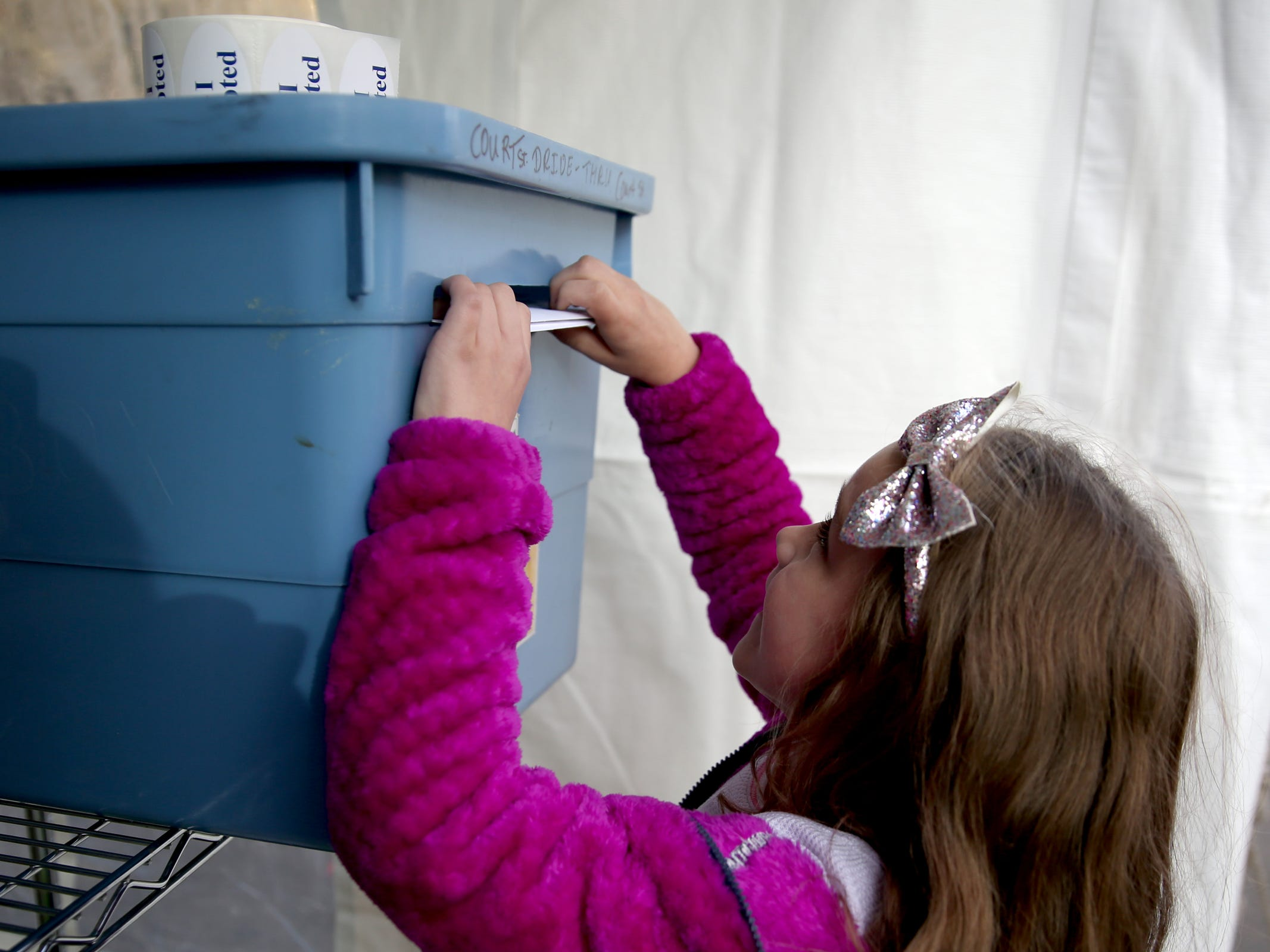 Addisun Rach, 7, of Salem, slips her dad's ballot inside a drop box at the drive-up drop box on Court St. NE in Salem on Election Day, Tuesday, Nov. 6, 2018.