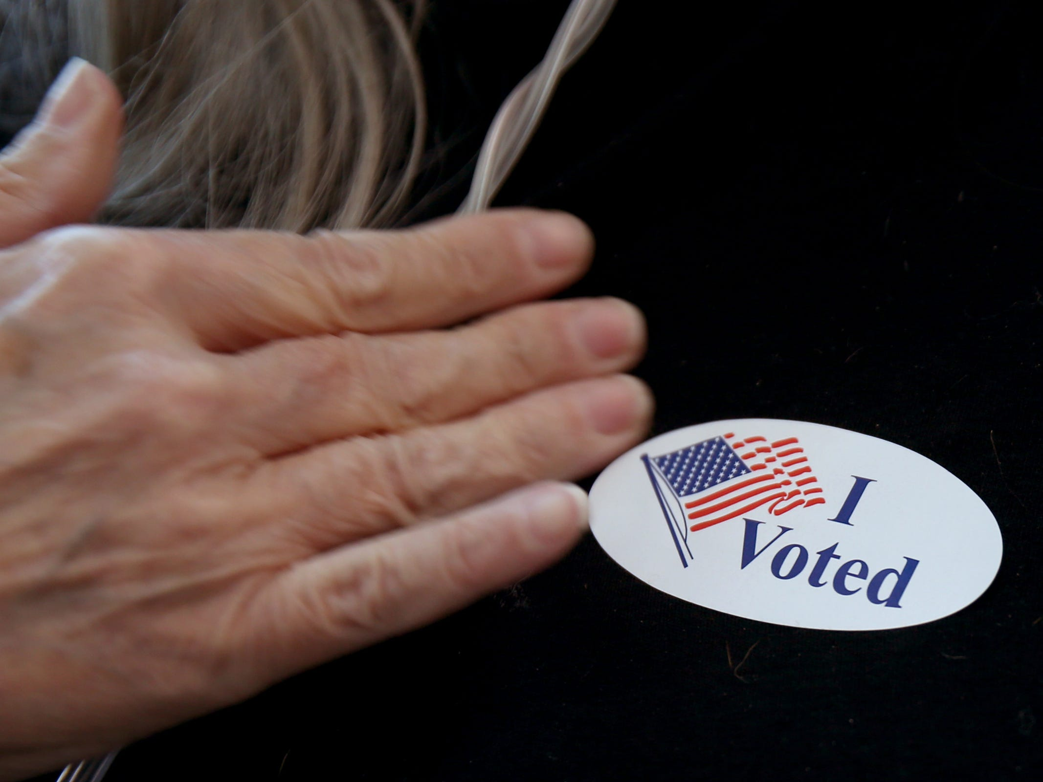 """Pam Laffitte, of Salem, puts on her """"I Voted"""" sticker after dropping off a ballot to a drop box in Salem on Election Day, Tuesday, Nov. 6, 2018."""