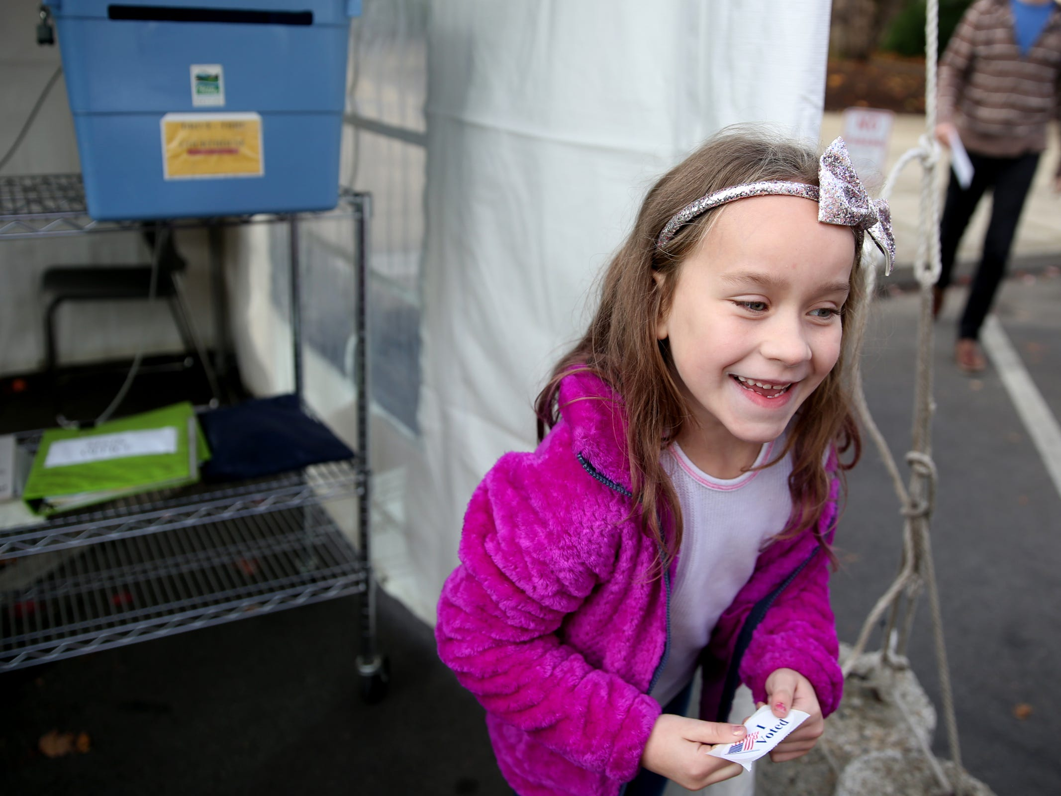 Addisun Rach, 7, of Salem, gets a sticker after slipping her dad's ballot inside a drop box at the drive-up drop box on Court St. NE in Salem on Election Day, Tuesday, Nov. 6, 2018.