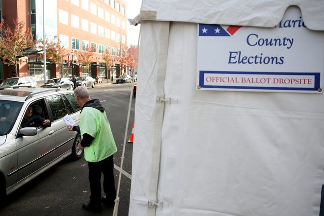 Doug Leaf, a ballot box security guard, grabs ballots from voters at the drive-up drop box on Court St. NE in Salem on Election Day, Tuesday, Nov. 6, 2018.