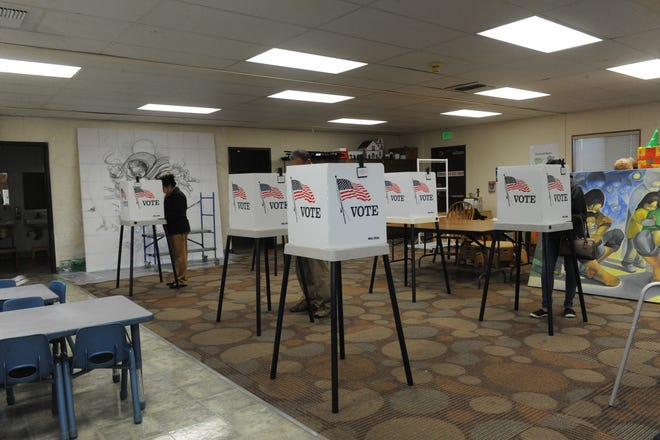 Voters cast their ballots at Sherwood Elementary School in Salinas on Tuesday, with artwork from Jose Ortiz's Hijos del Sol Arts Productions serving as the backdrop.